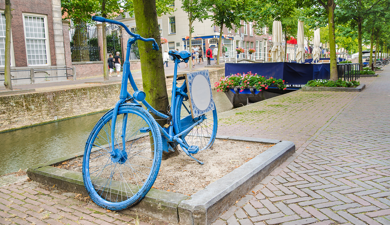 Old Dutch blue bicycle parked by a canal in Delft