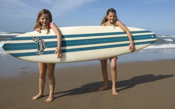 Girls on beach posing with surfboard