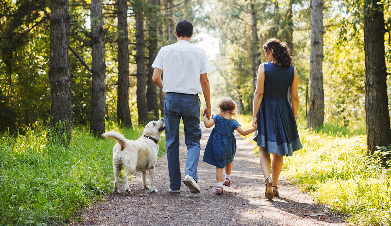 Family walking with dog and child.
