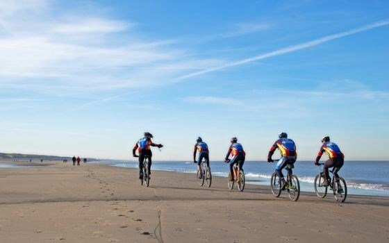 Group of cyclists on the beach of Noordwijk