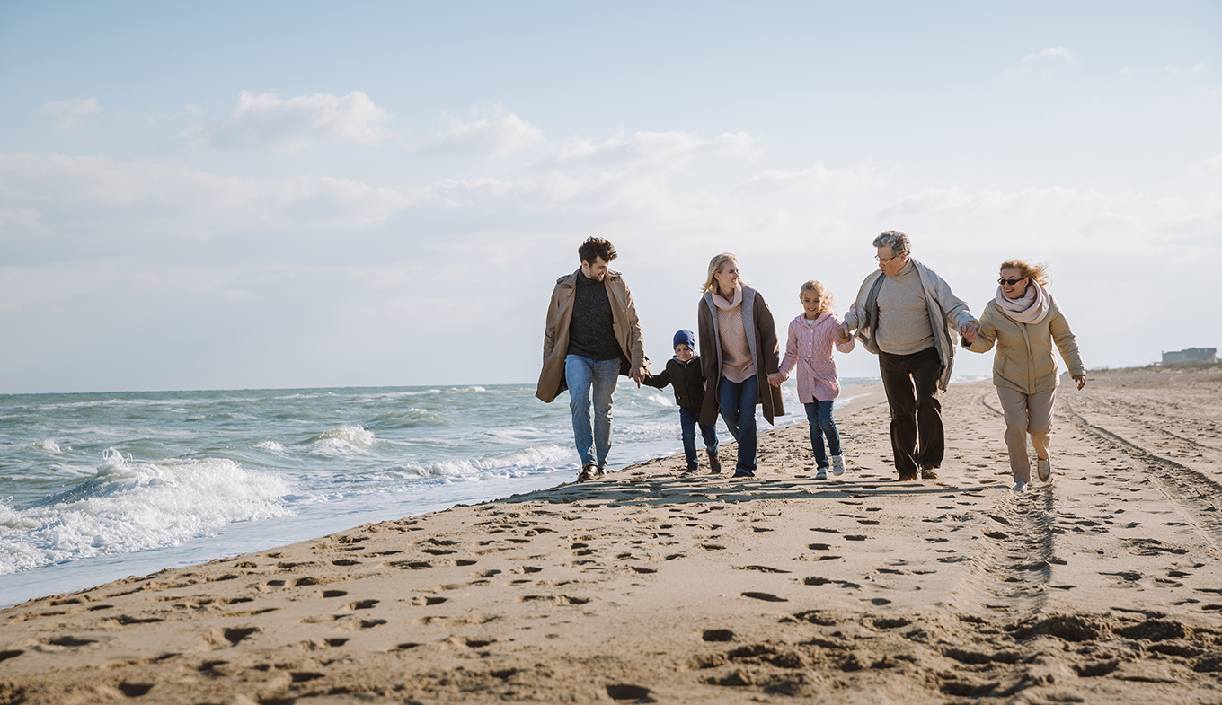Family walking on the beach with grandparents