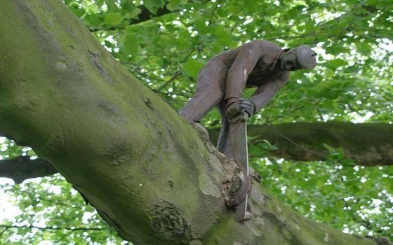 A statue of a man sawing off the branch he is standig on