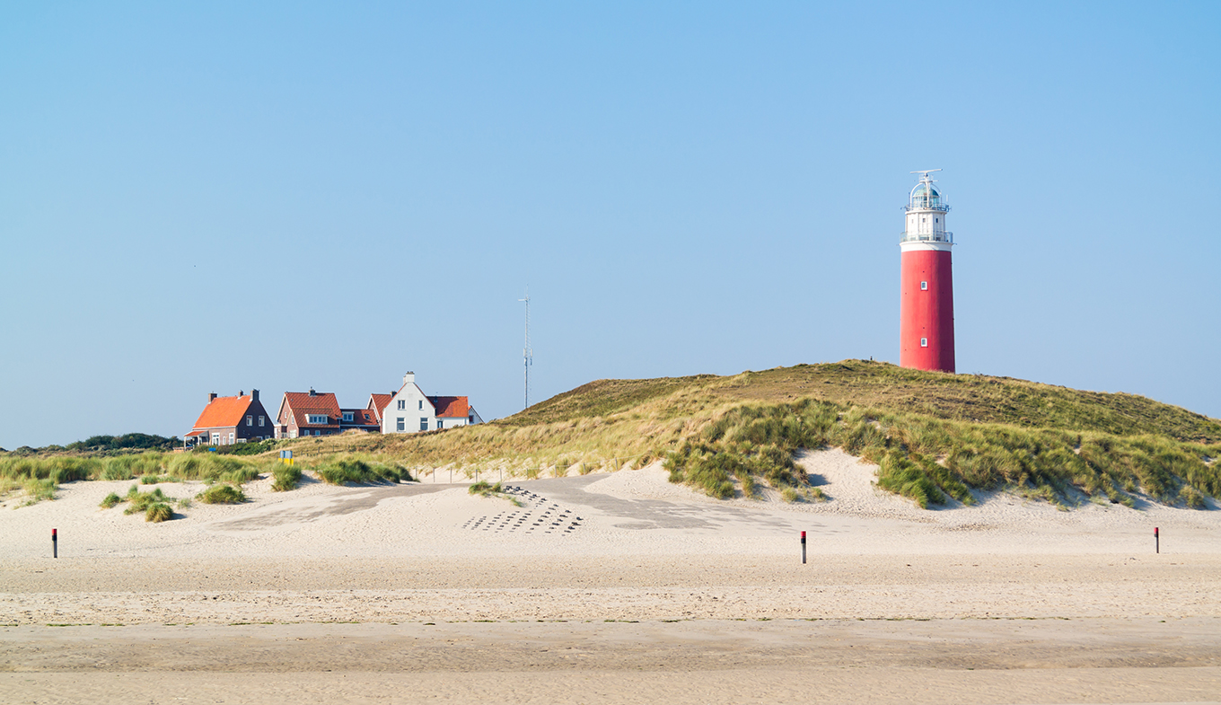 View from beach dunes with white and red lighthouse on Texel
