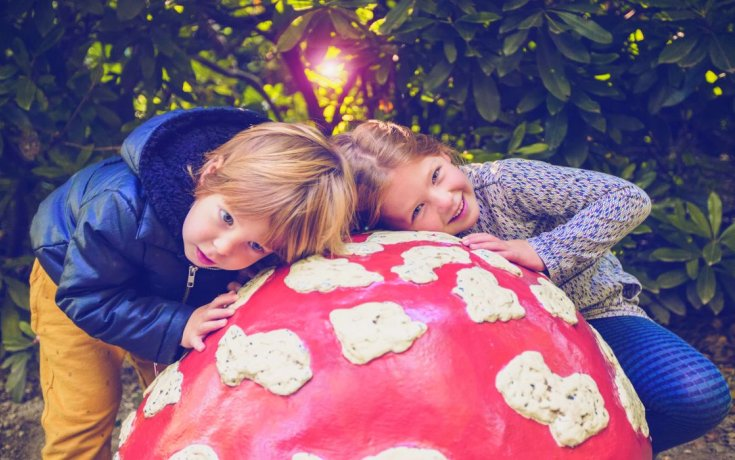 Children resting on red mushrooms in the Efteling