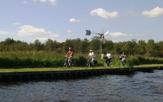 People cycling alongside the water