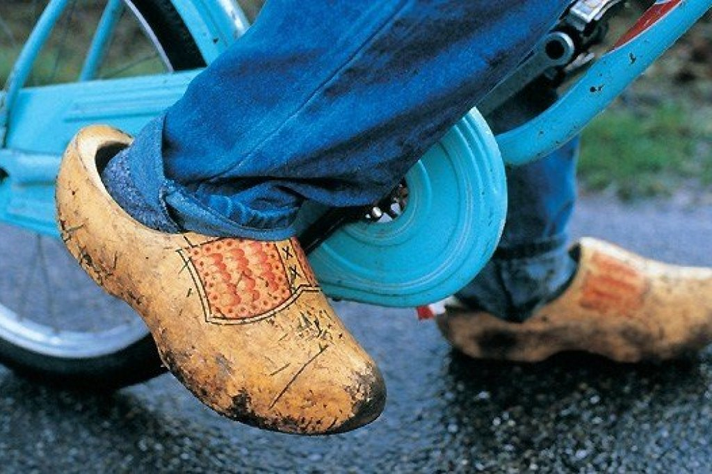 A man wearing clogs cycling