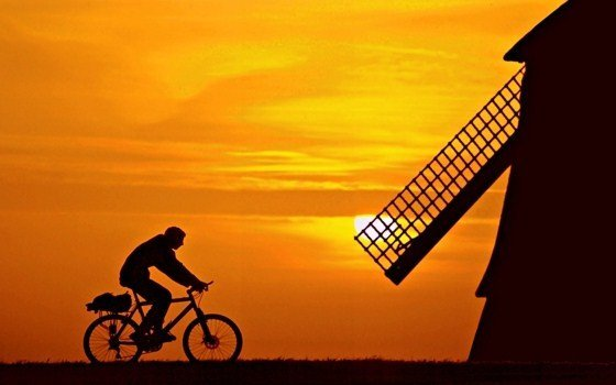 Silhouette of a Mill and Cyclist at sunset